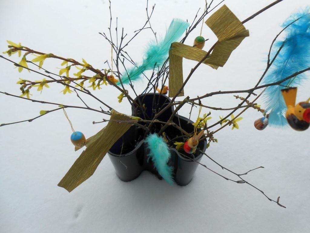 Osterzweige werden in Vasen gestellt und mit bunten Federn und Krepp- oder Seidenpapier geschmückt.